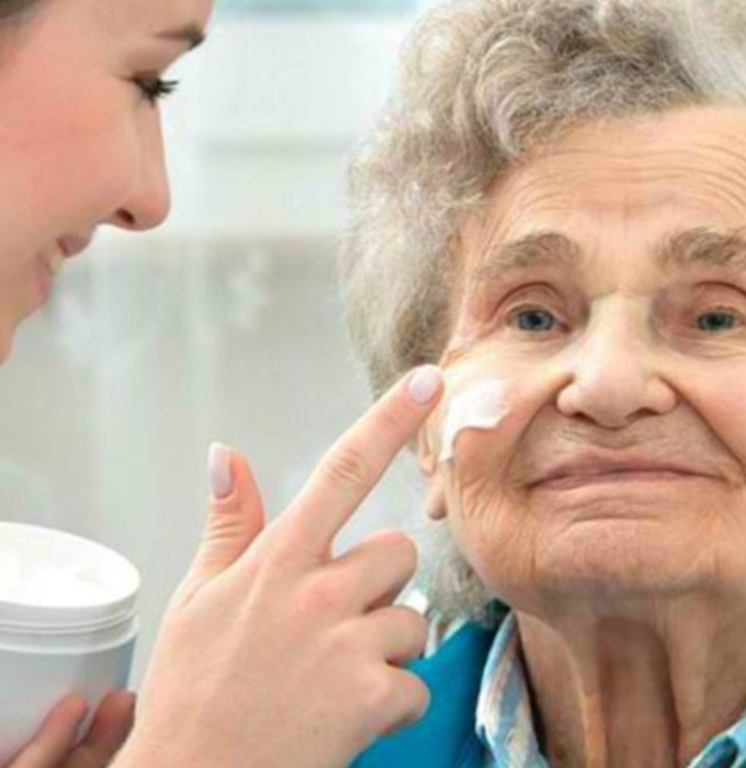 Nurse assistant applying facial cream to elder lady